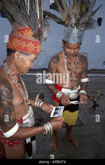 Malaysia Borneo Sarawak Kuching Iban tribesmen warriors by cruise ship looking at Polaroid photo - Stock Image
