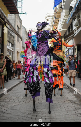 Street performers dancing on stilts on Calle Obispo, or Bishop street, one of the most famous and traveled streets - Stock Image