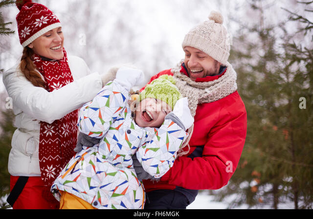 Happy parents playing with carefree daughter in park - Stock Image