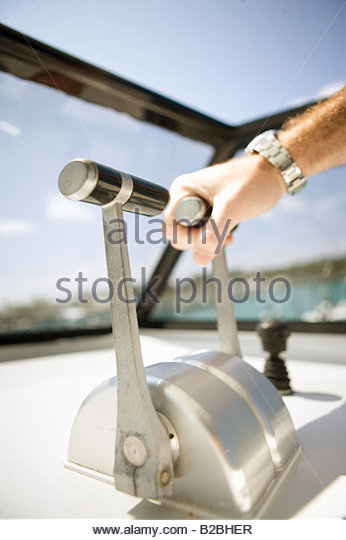 Man's hand on boat throttle - Stock Image