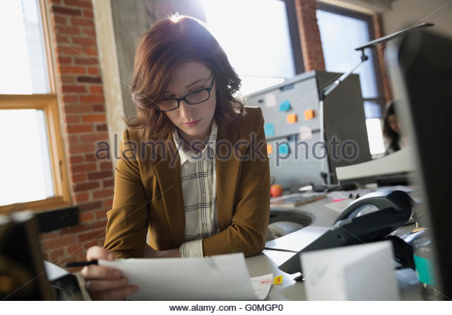 Focused businesswoman reading paperwork at office desk - Stock Image