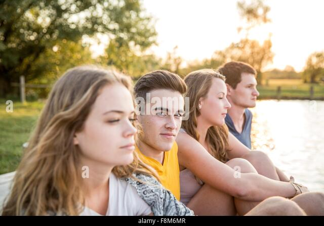Group of friends sitting by lake, relaxing - Stock Image