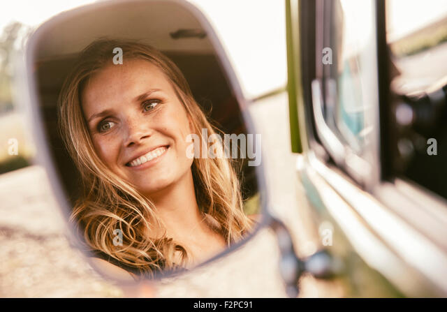 Face of smiling woman reflected in wing mirror of van - Stock Image
