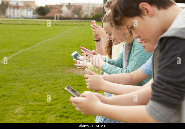 Row of five boys and girls reading smartphone text messages at football pitch - Stock Image