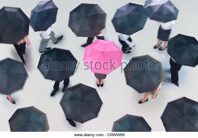 Businesswoman with pink umbrella surrounded by business people walking with black umbrellas - Stock Image
