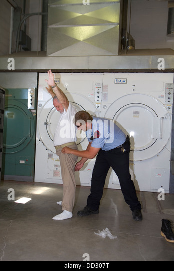 Sergeant searching inmate that is leaving his work assignment. Searches are crucial to maintain high security and - Stock Image