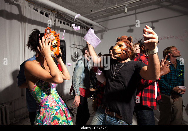 People wearing lion and tiger masks dancing at party - Stock Image