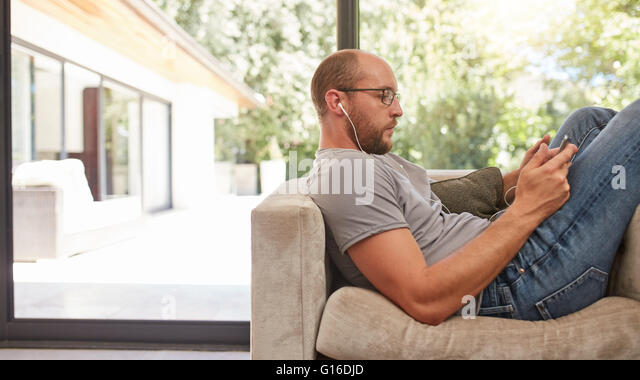 Side view image of a man using his tablet while sitting on the sofa at home. Caucasian man relaxing on couch using - Stock Image
