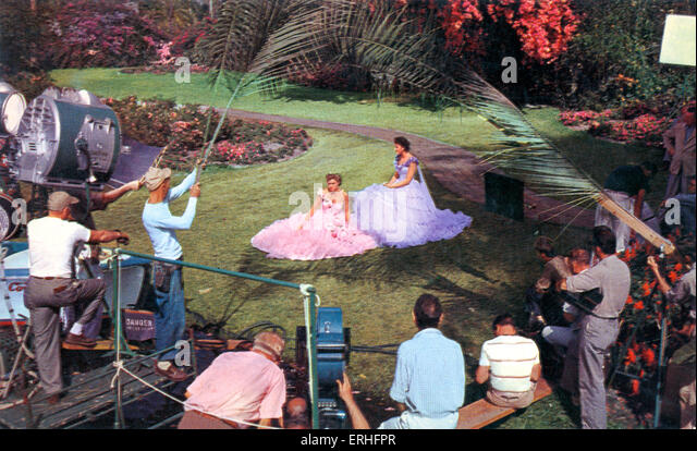 Hollywood movie set. Two unidentified actresses being filmed surrounded by film crew, 1950 s. - Stock-Bilder