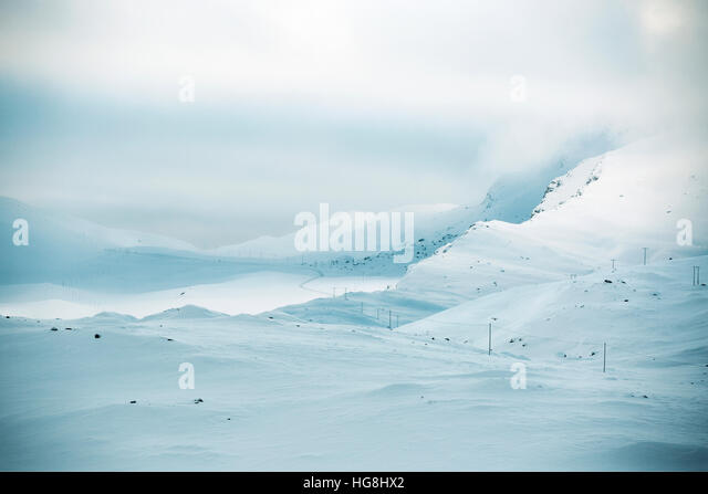 A road goes through snow covered mountains with stormy clouds in Norway. - Stock-Bilder