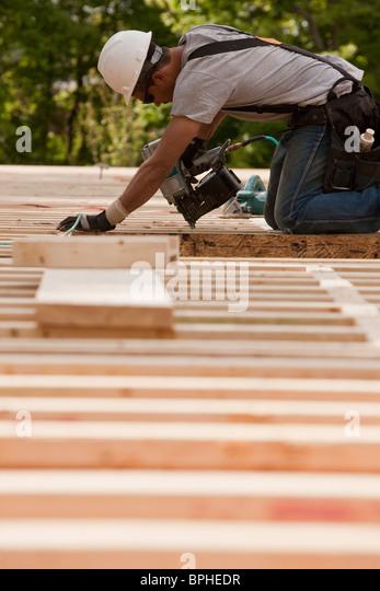 Carpenter using a nail gun at a construction site - Stock-Bilder