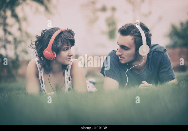 Boy and girl  listening to music on headphones - Stock Image