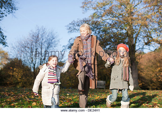 Grandmother holding hands with granddaughters - Stock Image
