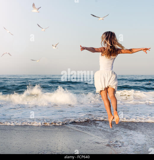 Beautiful girl  jumping on sea - Stock Image