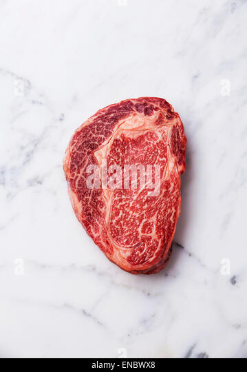 Raw fresh marbled meat Black Angus Steak Ribeye on white marble background - Stock Image