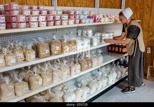 Illinois Arthur Shady Crest Orchard & and Farm Market woman Amish cap bonnet employee job working stocking shelves - Stock Image