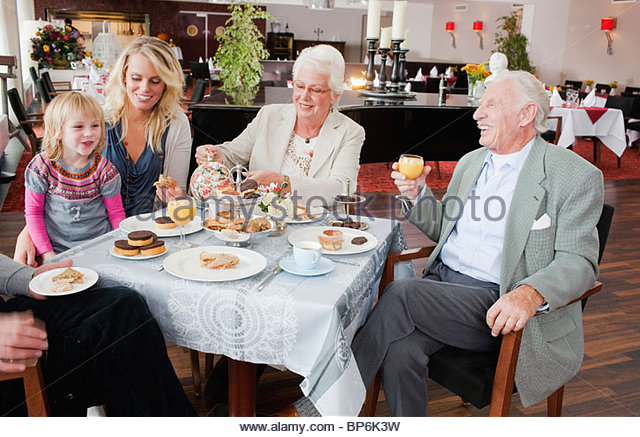 A three generation family having afternoon tea in a restaurant - Stock Image
