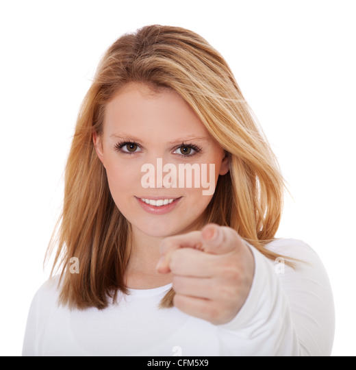 Attractive teenage girl points with finger. All on white background. - Stock Image
