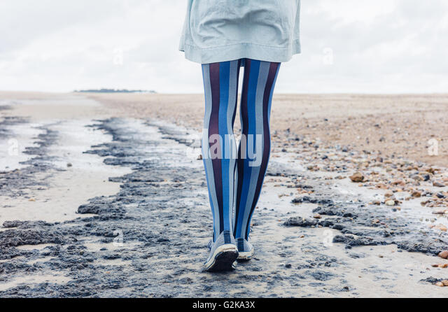 The legs of a young woman as she is walking on the beach - Stock Image
