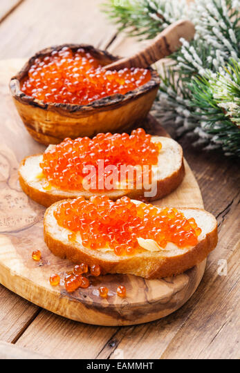 Sandwiches with Salmon red caviar and green Fir Christmas branch on wooden background - Stock Image