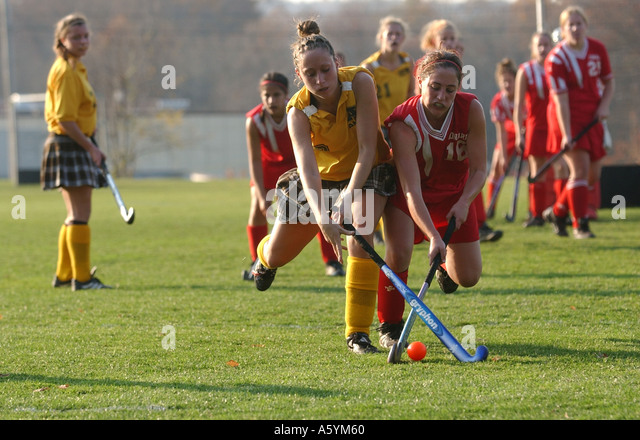 Girls Field Hockey players battle for the ball in the midfield - Stock Image
