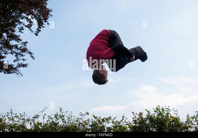 Man on a trampoline upside down doing a forward roll somersault in mid air above a hedge against the blue sky. England, - Stock Image