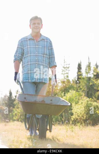 Portrait of male gardener pushing wheelbarrow at garden - Stock Image