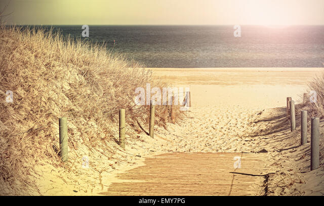 Retro toned panoramic photo of a beach path, old film filter applied. - Stock-Bilder