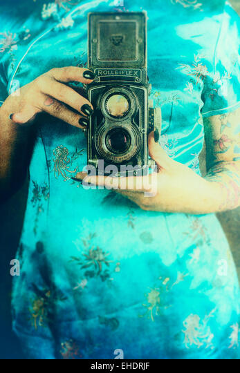 Woman wearing a Chinese dress holding a vintage Rolleiflex camera - Stock Image