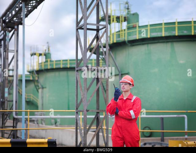 Worker with radio in front of oil tanks - Stock-Bilder