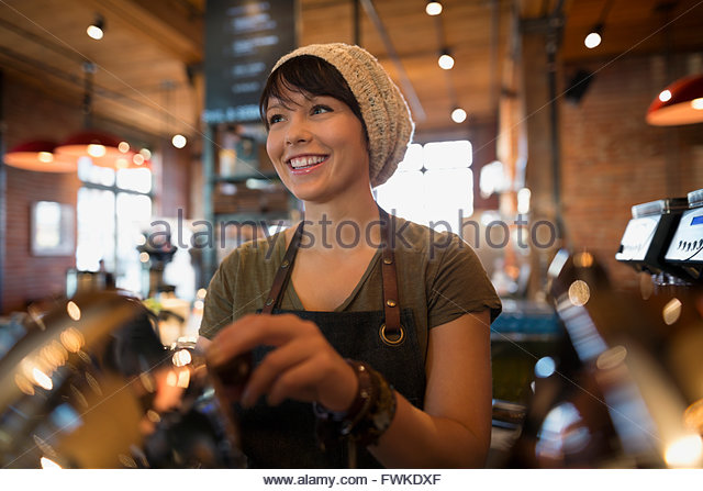 Smiling barista working in coffee shop - Stock Image