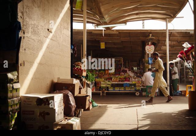 A male Arab walks along one of the corridors at Deira's Fruit and Vegetable Market. Dubai, UAE. - Stock-Bilder