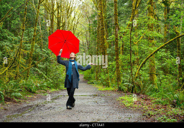 Woman on forest path with red umbrella - Stock Image