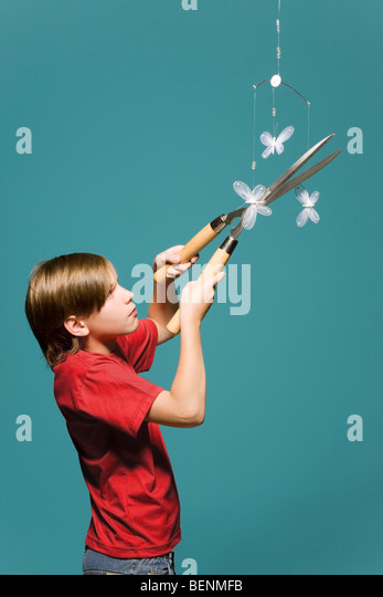 Boy using hedge clippers to cut down butterfly mobile - Stock Image