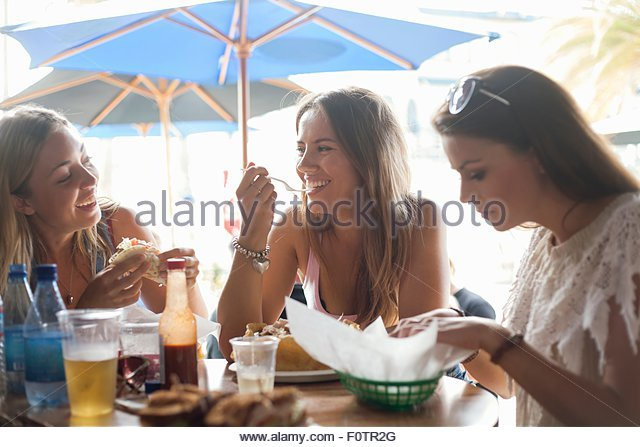 Three young women sitting at cafe, eating lunch - Stock-Bilder
