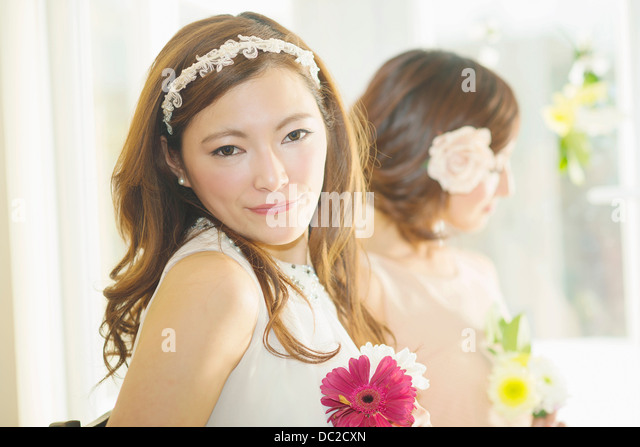 Women accessorized with fake flowers - Stock Image
