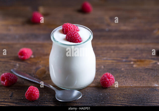 White yogurt with raspberries in glass bowl on rustic table. - Stock Image