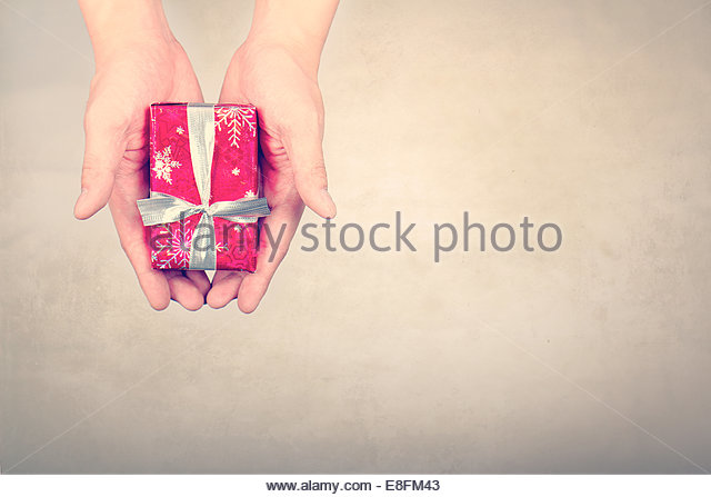 Overhead view of Hands Holding wrapped christmas gift - Stock Image