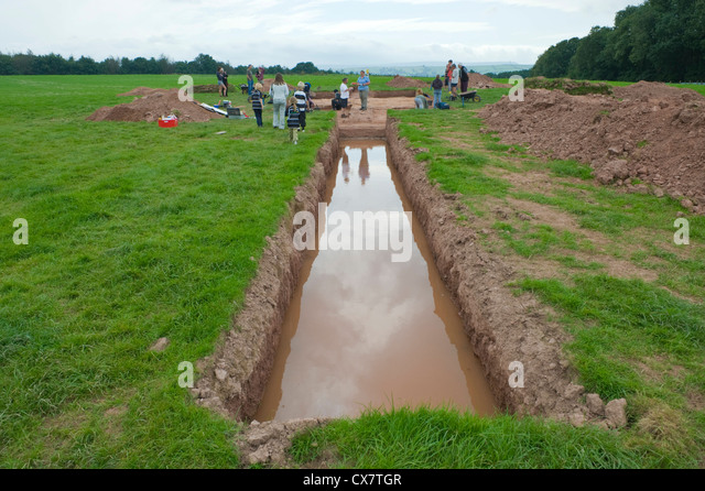 Flooded trench on archaeology dig of prehistoric neolithic site on Dorstone Hill Herefordshire England UK - Stock Image