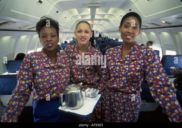 Jamaica Montego Bay onboard Air Jamaica flight attendants stewardess Black females commercial airliner in flight - Stock Image
