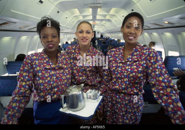 Jamaica Montego Bay onboard Air Jamaica flight attendants stewardess Black females commercial airliner in flight - Stock Image