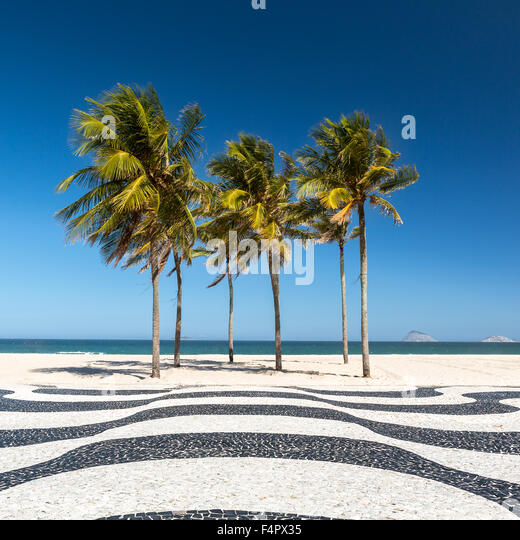 Palm trees and the iconic Copacabana beach mosaic sidewalk, in Rio de Janeiro, Brazil. - Stock Image