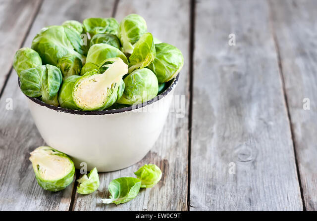 Brussels sprout in small rustic bowl on old wooden table. Copy space background. - Stock Image