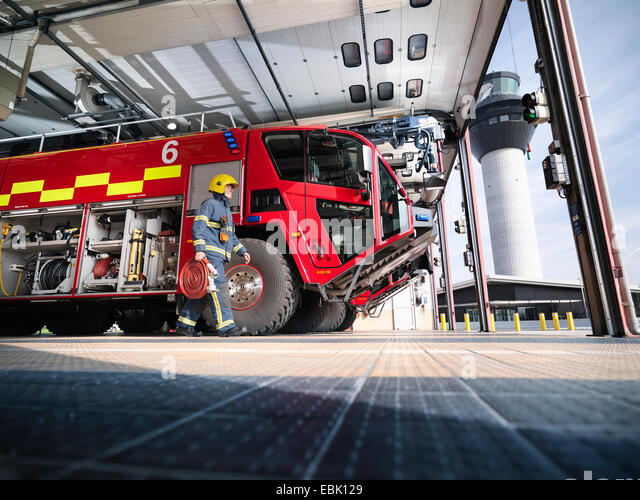 Fireman carrying equipment to fire engine in airport fire station - Stock Image