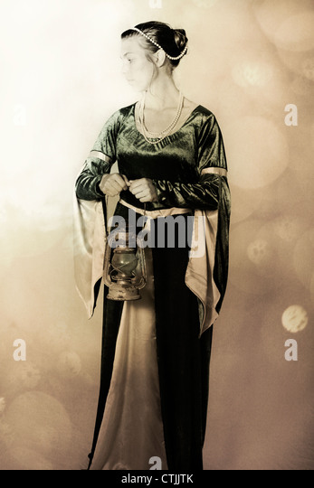 a woman in a Victorian dress with an old lantern - Stock Image