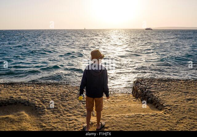Young boy standing by sea, looking at view, rear view, Hurgada, Red Sea, Egypt - Stock Image