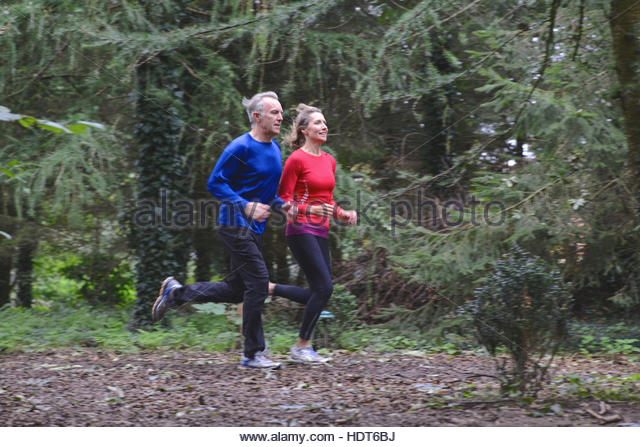 Mature married couple jogging in forest. - Stock Image