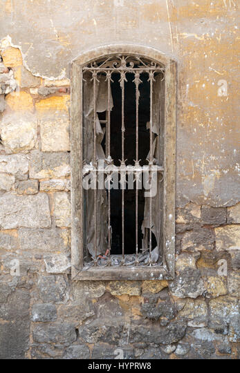 Old abandoned wall with one closed wooden window covered by broken wooden iron grid, Old Cairo, Egypt - Stock Image