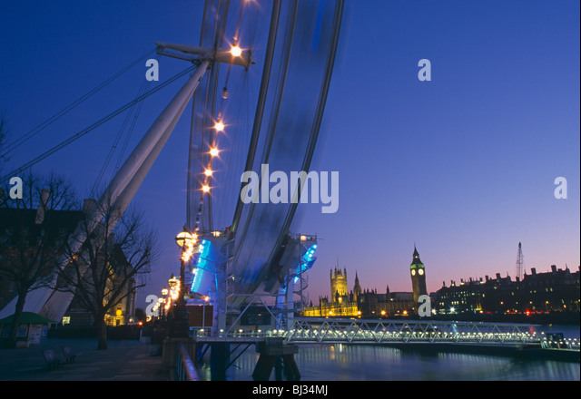 The ever-turning London Eye is seen over the River Thames with the Palace of Westminster and Parliament beyond. - Stock-Bilder