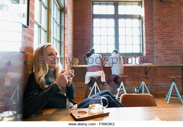 Smiling young woman drinking tea in coffee shop - Stock Image